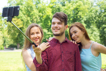 Best friends using selfie stick and make a joint photo mobile phone - concept  friendship, fun , travel with young people together.