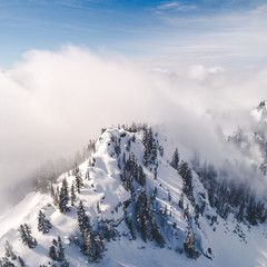 Stylized Aerial Vew of Snowy Mountain Top and Hazy Fog Clouds