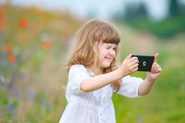 little girl is taking photo with mobile phone camera outdoor in nature