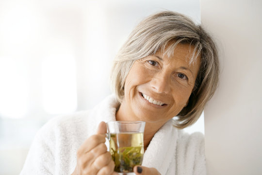 Senior woman in bathrobe drinking hot green tea