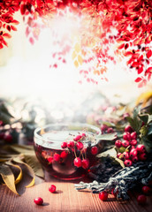 Cup of tea with scarf, autumn leaves and red berries  on wooden garden table. Hot autumn beverages concept