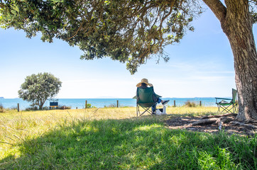 A women sitting under the tree and enjoying the beautiful landscape view of the ocean in New Zealand.