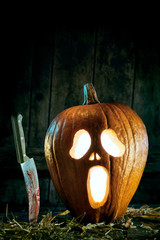 Halloween concept of spooky pumpkin with knife