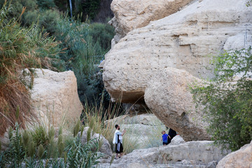 A man uses his mobile phone to take a picture as he visits Nahal David in the Ein Gedi Nature Reserve area