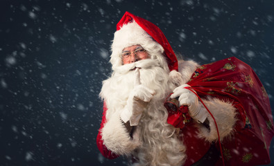 Santa Claus making a silence gesture, on dark background