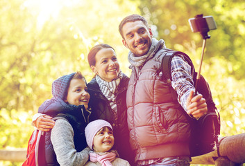 happy family with smartphone selfie stick at camp