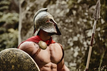 Portrait of anonymous muscular man wearing outfit of ancient gladiator posing in helmet with shield and spear in hands looking away. Spartan.