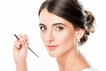 woman with eyebrows brush in hand