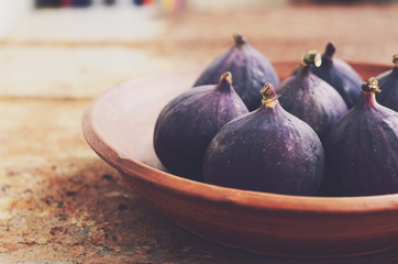 Ripe purple figs in clay bowl with empty space on rusty metal background