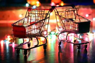 metal supermarket small cart on a background colored lights