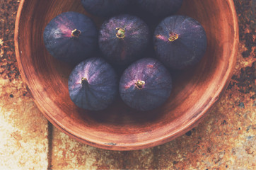Ripe fall figs in clay dish on rusted metal background
