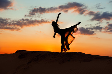Dancing at night in the sand against the backdrop of the setting sun, the silhouette of a dancer.
