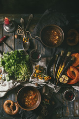 Fall holiday table decoration setting with bowls of hot carrot potato soup, baking pumpkin, carrot, garlic, fresh coriander, pretzels bread, red wine, berries and candle. Flat lay over wooden table