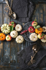Autumn holiday table decoration setting with decorative pumpkins, apples, red leaves with vintage cutlery, red wine, candle over wooden table. Rustic style. Flat lay