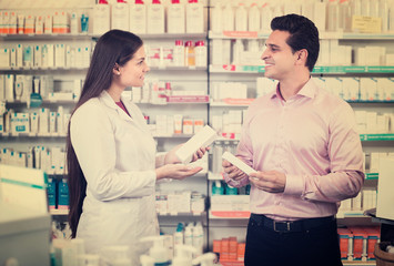 Pharmacist and customer in drugstore .