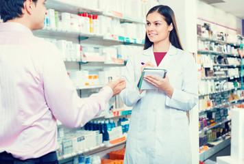 Pharmacist and customer in drugstore .