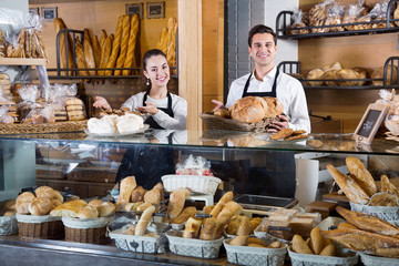Portrait of charming pleasant couple at bakery display