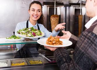 Girl and satisfied customer buying kebab