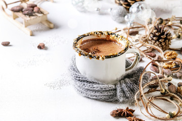 Vintage mug in wool scarf of hot chocolate, decor with nuts, caramel, spices. Ingredients and Christmas toys above over white texture background with space.