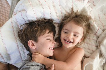 High angle view of smiling boy with brown hair and young girl lying on a bed, hugging.