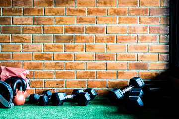 Brick wall with artificial grass and dumbbells on the foreground