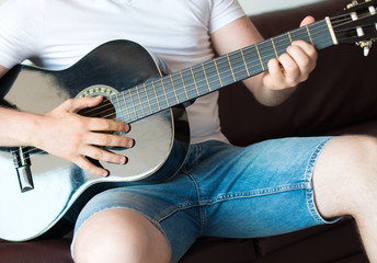 Unrecognizable man playing guitar at home.