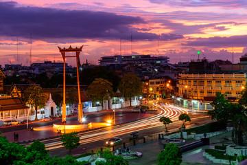 Giant swing landmark in Bangkok city in sunset time with blur moving lighting of car