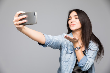 Beautiful brunette woman making a selfie blowing a kiss holding the smartphone isolated on a gray background