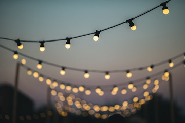 Outdoors wedding decoration with light bulbs at sunset Wall mural