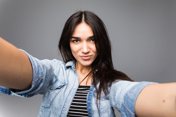 Portrait of a cheerful young woman making selfie photo over gray background