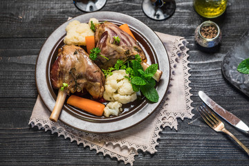 Lamb shank dinner on slate tray with vegetables, parsley and mint jam on black rustic wooden table, top view, copy space