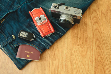 top view. passport book insert on pocket jean pants with retro camera,toy car and key placed on top of them. wooden are background. image for wear, equipment, accessory, fashion, travel concept