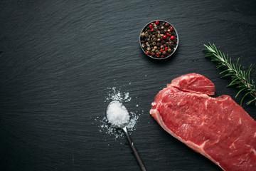Raw beef steak on black slate background