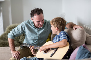Son playing guitar with Father