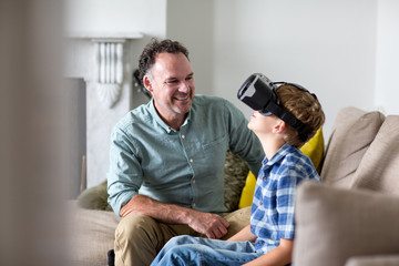 Boy using a VR headset game at home with Father