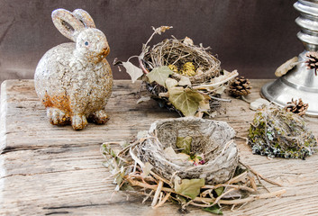 decoration with bird nests , dried flowers, and a funny,fatty,rabbit on textured old table.