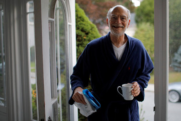 Michael Rosbash, a Brandeis University professor, retrieves the morning newspaper after learning he is one of the 2017 Nobel Prize in Physiology or Medicine winners, at his home in Newton, Massachusetts