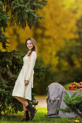 Young lady near lunch table in autumn surround