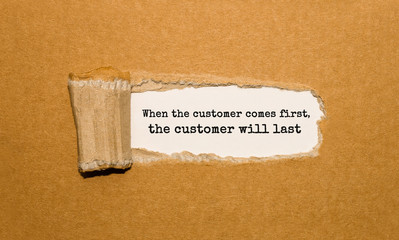 The text When the customer comes first the customer will last appearing behind torn brown paper