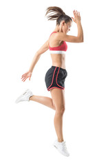 Fit active sport woman running stopped motion looking down. Full body length portrait isolated on white studio background.