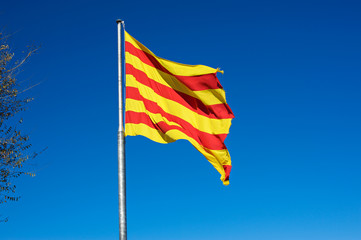 The flag of Catalonia isolated on blue sky waving on wind.