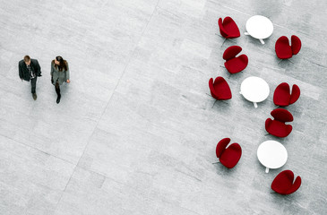 View from above of lobby with armchairs, tables and blurred pair of people passing by