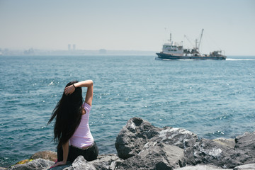 The tourist admires the sea view. Active tourism. The girl looks at the ship floating on the horizon