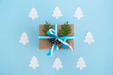 Gift box wrapped of craft paper, blue and white ribbons and decorated fir branches and pinecones on the blue background with white paper fir tree, top view. Christmas present.