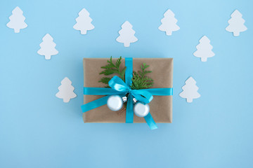 Gift box wrapped of craft paper, blue ribbon and decorated fir branches and silver Christmas balls on the blue background with white paper fir tree, top view. Christmas present.