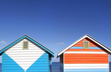 Two vibrantly painted beach huts on Melbourne's Brighton Beach