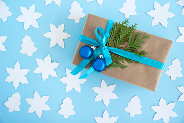Gift box wrapped of craft paper, blue ribbon and decorated fir branches and blue Christmas balls on the blue background with paper fir tree and star, top view. Christmas present.