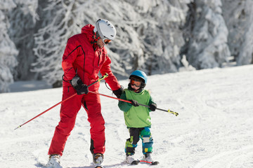 Skiing instructor with little boy