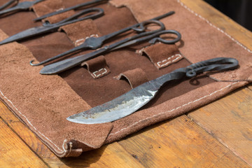 leather wrap of old medieval surgery doctors tools on wooden table, iron shears, knife, scissors and picks