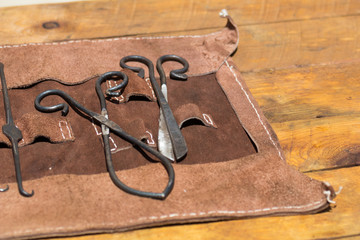 leather wrap of old medieval surgery doctors tools on wooden table, iron shears, scissors and picks